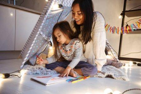 Photo pour Image d'une belle jeune femme asiatique avec sa petite fille s'amusant à dessiner dans l'album sur le sol. Concept de Noël . - image libre de droit
