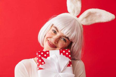Photo pour Joyeux jeune fille portant des oreilles de lapin de Noël debout isolé sur fond rouge, tenant boîte cadeau - image libre de droit