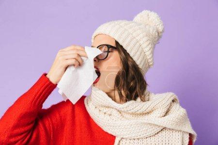 Photo pour Portrait d'une jeune femme malade portant un chapeau d'hiver isolé sur fond violet tenant une serviette . - image libre de droit
