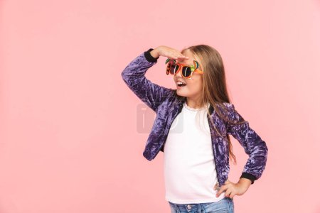 Photo pour Portrait d'une petite fille joyeuse portant des lunettes de soleil d'été debout isolé sur fond rose - image libre de droit