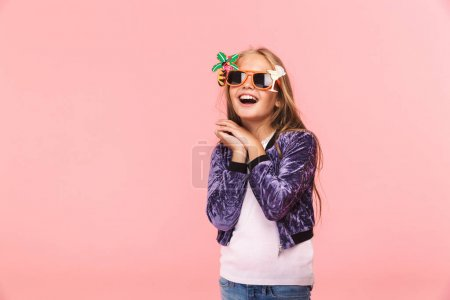 Photo for Portrait of a cheerful little girl wearing summer sunglasses standing isolated over pink background - Royalty Free Image