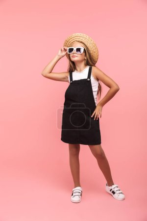 Photo for Full length portrait of a smiling little girl wearing summer sunglasses and hat isolated over pink background - Royalty Free Image