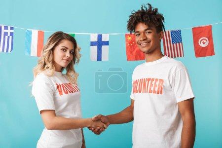 Foto de Feliz pareja multiétnica seguro de uso permanente de la camiseta de voluntarios aislado sobre fondo azul, estrechar las manos - Imagen libre de derechos