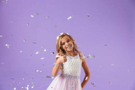 Photo pour Portrait d'une jeune fille jolie gaie souriante vêtue d'une robe de princesse isolée sur fond violet, montrant les pouces vers le haut - image libre de droit