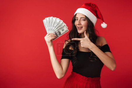 Photo for Cheerful young woman wearing Christmas hat standing isolated over red background, showing money banknotes - Royalty Free Image