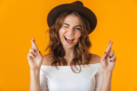 Photo for Portrait of a cheerful young woman wearing white shirt standing isolated over yellow background, holding fingers crossed for good luck - Royalty Free Image