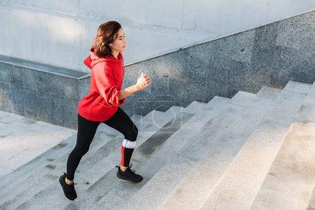 Photo pour Une jeune sportive confiante qui monte les escaliers en plein air - image libre de droit