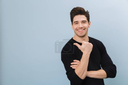 Photo for Portrait of a cheerful handsome young man standing isolated over blue background, pointing at copy space - Royalty Free Image