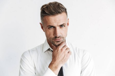 Photo for Handsome pensive businessman wearing formal clothes standing isolated over white background - Royalty Free Image