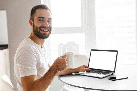 Photo for Happy handsome man freelancer sitting at the kitchen table, working on laptop computer, drinking coffee - Royalty Free Image