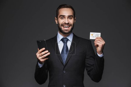 Photo for Portrait of a confident handsome businessman wearing suit isolated over black background, using mobile phone, showing plastic credit card - Royalty Free Image