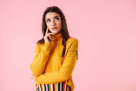 Photo for Beautiful pensive young woman wearing colorful clothes standing isolated over pink background - Royalty Free Image