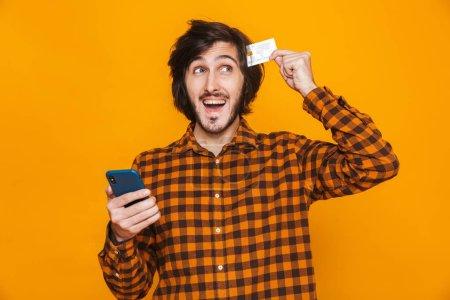 Photo pour Photo d'un homme ravi portant une chemise à carreaux tenant une carte de crédit et un smartphone tout en restant isolé sur fond jaune en studio - image libre de droit