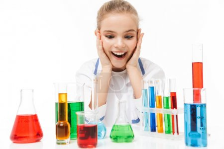 Photo for Image of cheerful school girl in white laboratory coat making chemical experiments with multicolored liquid in test tubes isolated over white background - Royalty Free Image