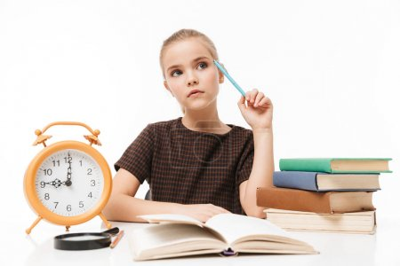 Photo for Portrait of happy school girl with big alarm clock on desk studying and reading books in class isolated over white background - Royalty Free Image