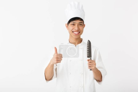 Photo for Excited asian chef wearing uniform standing isolated over white background, showing kitchen equipment - Royalty Free Image