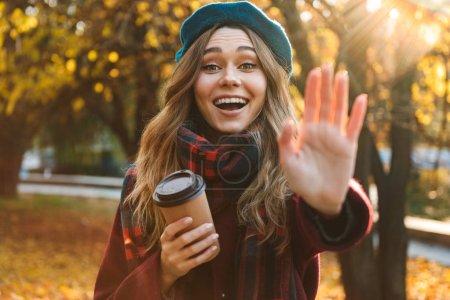 Photo pour Image d'une belle jeune femme heureuse de jolie marchant à l'extérieur dans le stationnement de ressort d'automne buvant le café en vous saluant. - image libre de droit