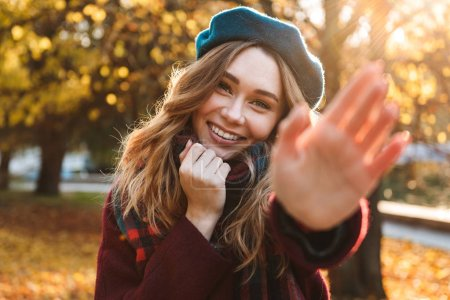 Photo pour Image of a beautiful happy young pretty woman walking outdoors in autumn spring park drinking coffee waving to you. - image libre de droit