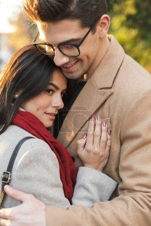 Photo for Portrait of casual romantic couple man and woman 20s smiling and hugging each other while walking in autumn park - Royalty Free Image