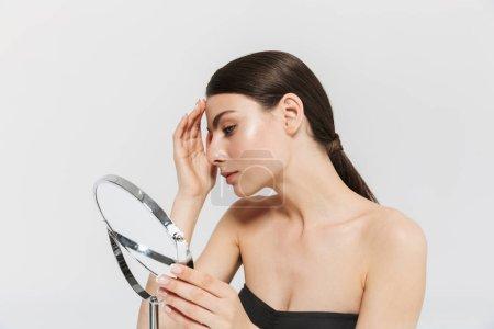 Photo pour Portrait de beauté d'une jolie jeune femme isolée sur fond blanc, regardant le miroir, examinant le visage - image libre de droit