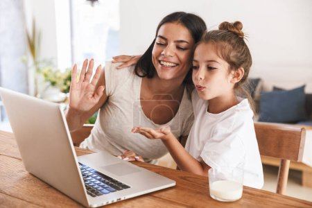 Photo for Image of happy family woman and her little daughter smiling and waving at laptop computer together while sitting at table in apartment - Royalty Free Image