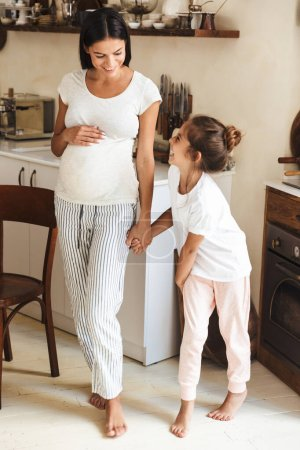Photo for Full length image of attractive family little girl smiling and standing with her pregnant mother at cozy apartment - Royalty Free Image