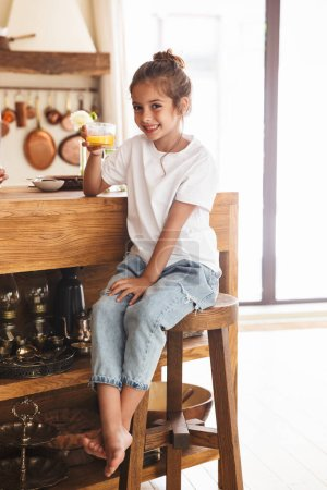 Photo for Portrait of beautiful little girl having breakfast and drinking orange juice while sitting at table in bright kitchen at home - Royalty Free Image
