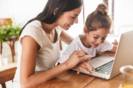 Photo for Image of beautiful family woman and her little daughter smiling and using laptop computer together while sitting at table in apartment - Royalty Free Image