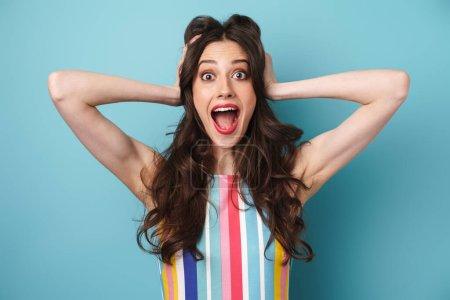 Photo pour Photo de belle femme excitée en robe rayée saisissant sa tête et exprimant surprise isolé sur le mur bleu - image libre de droit