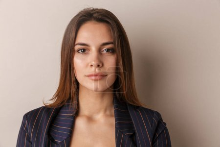 Photo for Photo of young businesswoman in formal suit posing and looking at camera isolated over white background - Royalty Free Image