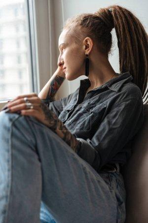 Photo pour Photo d'une incroyable jeune fille concentrée avec dreadlocks à l'intérieur posant en regardant la fenêtre . - image libre de droit