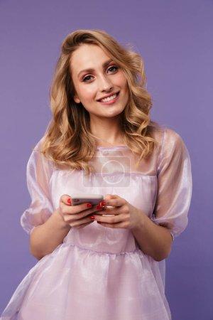Photo pour Image d'une jeune femme heureuse souriante et tapant sur smartphone isolé sur fond violet - image libre de droit