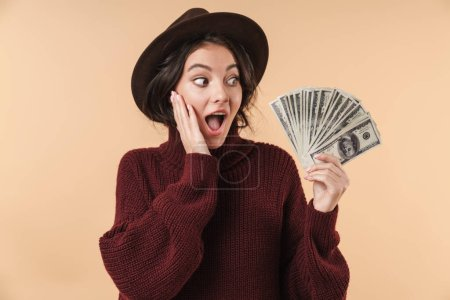 Image of young surprised emotional brunette woman isolated over beige wall background holding money.