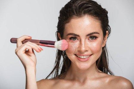 Photo pour Portrait de beauté d'une jolie jeune femme sensuelle souriante aux cheveux longs brune mouillée se tenant isolée sur fond gris, à l'aide d'une brosse de maquillage - image libre de droit