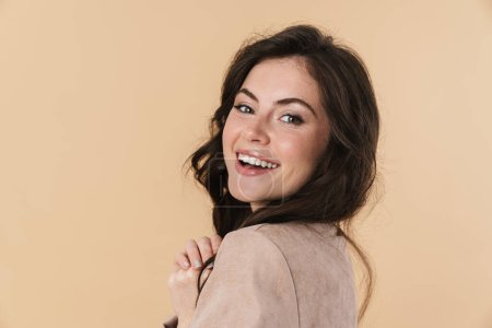 Image of happy caucasian woman smiling and looking at camera isolated over beige background