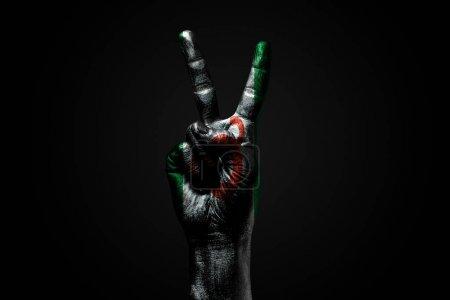 Photo pour Une main avec un drapeau d'Ingouchie dessiné montre un signe de paix, un symbole de paix, d'amitié, de salutations et de paix sur un fond sombre. Cadre horizontal - image libre de droit