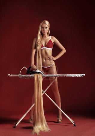 Conceptual picture of a blond woman ironing her hair