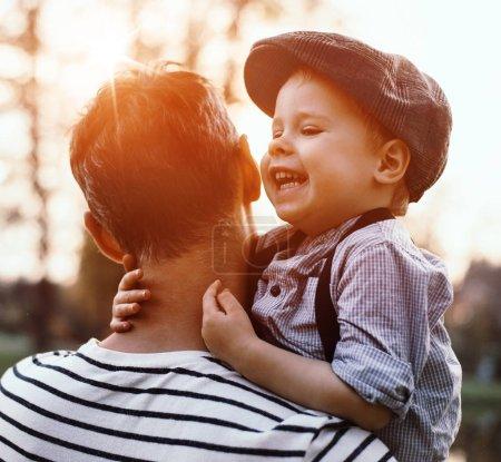 Photo pour Beau portrait d'un mignon petit garçon embrassant son père - image libre de droit