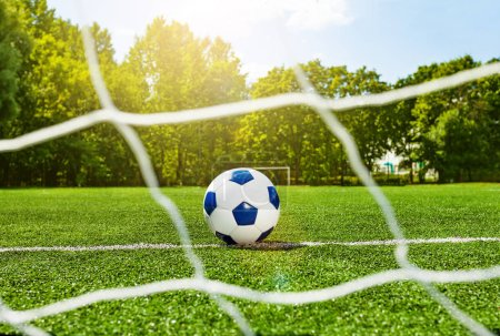 Football soccer children school ball behind the gate net on stadium field