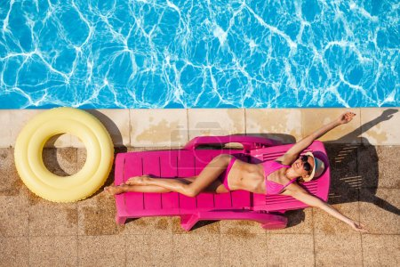 High angle shot of happy young woman in pink bikini relaxing on sun bed by the swimming pool