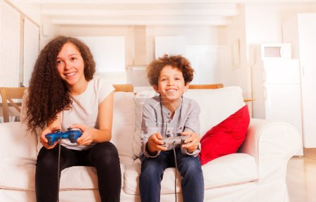 Portrait of happy children, teenage girl and preteen boy, sitting on the sofa, playing video games