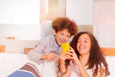 Photo for Curly-haired teenage boy and girl having fun  surfing internet using smart phone, sitting on the coach at home - Royalty Free Image
