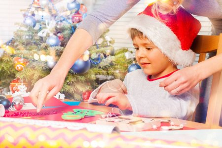 Woman helping her little son to decorate holiday ornaments