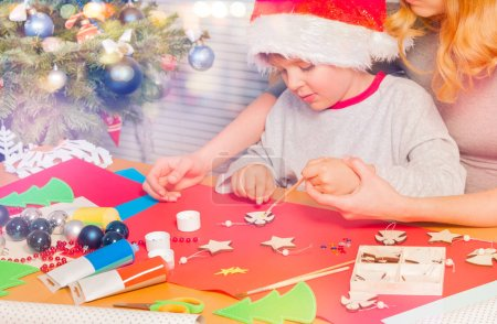 Woman helping little boy decorate Christmas ornament with white paint