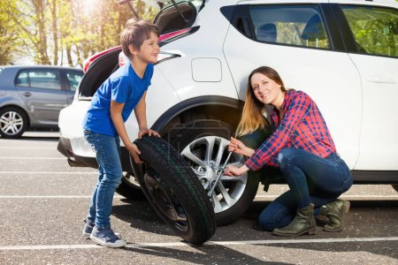 Photo for Portrait of happy young mother and her little son changing flat tire together outside - Royalty Free Image