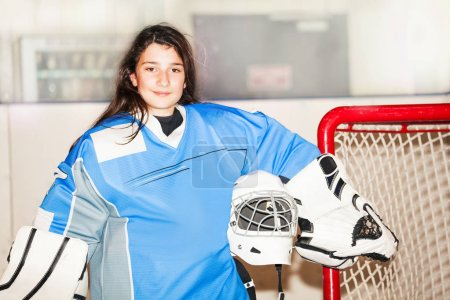 Photo for Portrait of happy teenage girl goaltender, standing next to the net and holding helmet in her hand after hockey match - Royalty Free Image