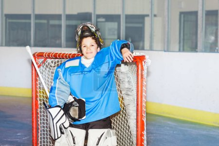 Portrait of teenage boy goaltender, standing next to the net after hockey match smiling