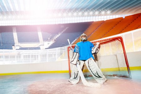 Portrait of young goalie guarding his net during the game at ice hockey arena