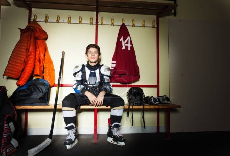 Photo for Portrait of teenage boy preparing for ice hockey game in locker room - Royalty Free Image