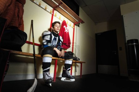 Photo for Side-view portrait of teenage boy sitting on the bench in ice hockey dressing room - Royalty Free Image